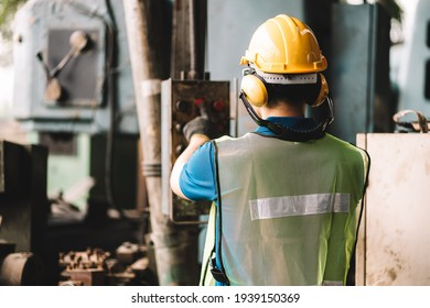 Back view of Work at factory.Asian worker man  working in safety work wear with yellow helmet .in factory workshop industry machine professional