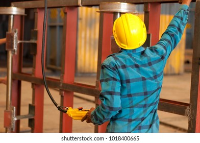 Back view if worker in yellow safety helmet controlling crane for lifting steel inside production department in heavy industry factory