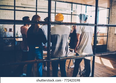 Back view of working team discussing ideas and strategies for startup project  meeting at coworking space, rear view of young crew solving problems sharing opinions  with each other during consultancy