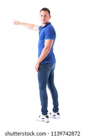 Back view of young adult casual man turning and looking at camera showing directions with hand gesture. Full body isolated on white background.