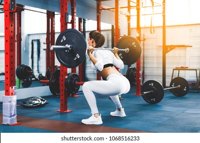 Back view young adult girl doing squat in gym with barbell. Fit woman in great shape. The development of leg muscles, strengthening of the spine after injuries