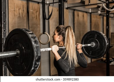 Back view young adult girl doing heavy duty squat in gym with barbell. Woman with perfect abs doing squat exercises. Blonde fit woman in great shape. Fitness