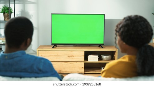 Back view of young African American family couple watching TV with chroma key while resting at home sitting on sofa in room. Wife and husband spending time together watch television with green screen