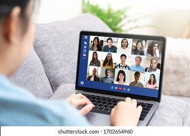 Back view of young asian business woman work remotely at home video conference remote call to corporate group. Meeting online,videocall, group discuss online concept with screen of teamwork on laptop.
