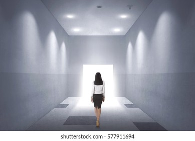Back view of a young asian business woman walking to opened door in the office