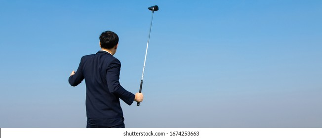 Back view of Young Asian CEO Businessman wearing suits playing golf at the golf course. Portrait of Asian businessman. sucess and happy time