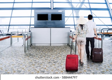 Back view of a young Asian couple walking in the airport terminal while carrying suitcases for holiday