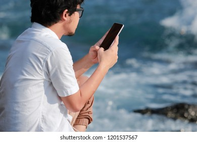 Back view of young Asian man using mobile smart phone at sea shore. Internet of things concept.
