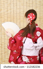 Back view of young asian woman in traditional clothes of kimono holding paper fan