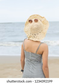 back view of young asian woman in straw hat on tropical  beach