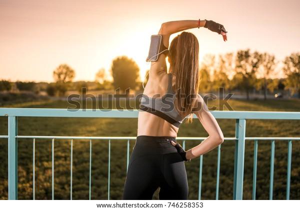 Back view of young athlete woman exercising outdoors.