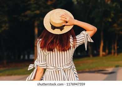 back view of young attractive woman dancing in the park wearing striped dress and straw hat