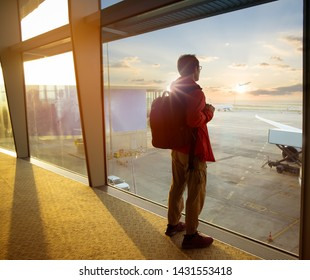 Back view of young  backpacker man which take a picture on the window by smartphone at a terminal airport