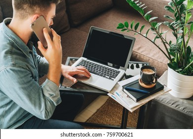 Back view. Young bearded hipster man, dressed in denim shirt, sits at home on couch at coffee table, uses laptop and talks on his cell phone, calling. Online marketing, education, e-learning. Startup.