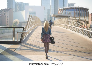 back view of young beautiful caucasian blonde girl walking through the streets of the city wearing a jeans shirt and a floral skirt - youth, freshness, carefreeness concept