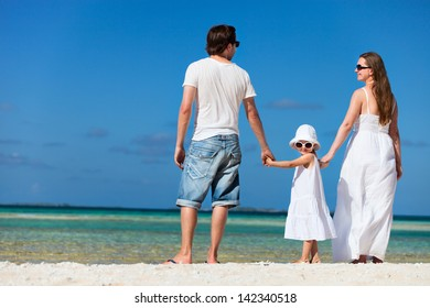 Back view of young beautiful family on tropical beach