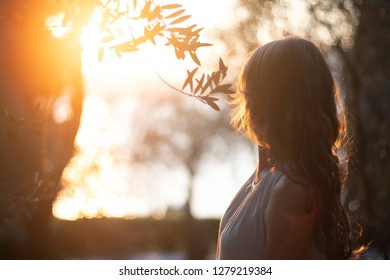 Back view of a young beautiful woman at the sunset and looking to the  sea horizon.