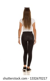 back view of young beautiful woman in black tight jeans posing on white background