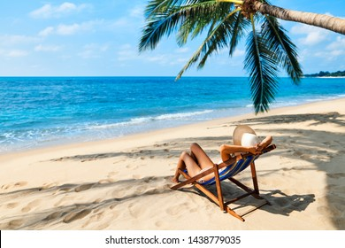Back view of young beautiful woman sunbathe and relax on tropical beach with copy space. Summer vacation concept