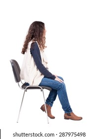back view of young beautiful  woman sitting on chair.  girl  watching. Rear view people collection.   girl in a white tank top sitting on a stool and looking to the right.