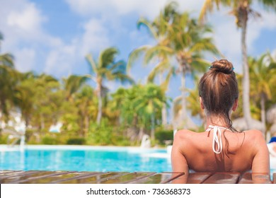 back view of young beautiful woman relaxing in spa pool