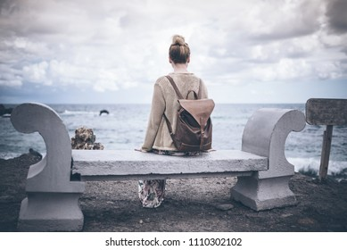 back view of young blond woman in long dress and with backpack sitting on stone bench by sea