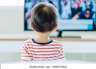 Back view of young boy is watching a television screen.Concept for a tv effect on children or a communication concept.