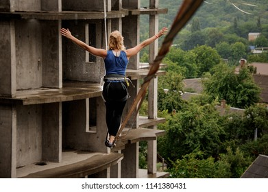 Back view of a young brave woman balancing on a slackline against the background of high empty building