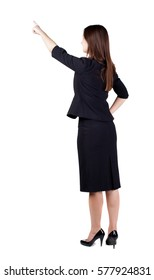 Back view of young brunette business woman pointing at wall. beautiful girl in dark suit. Rear view people collection. backside view of person. Isolated over white background.