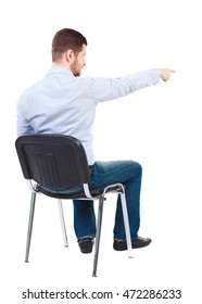 back view of young business man sitting on chair and pointing. Rear view people collection. Bearded businessman sitting on a chair and shows a finger forward.