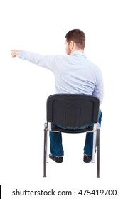back view of young business man sitting on chair and pointing. Bearded businessman in white shirt sitting on chair and pointing her finger.