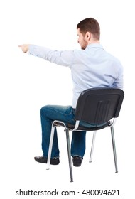 back view of young business man sitting on chair and pointing. Bearded businessman sitting on a chair and shows a finger forward.