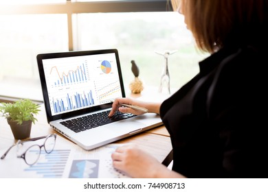 Back view of young business woman, hand-held, pen notes notebook on laptop computer with blank copy space on the screen, selective focus.