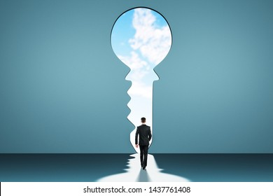 Back view of young businessman in abstract blue interior with keyhole window and sky view. Access and success concept.
