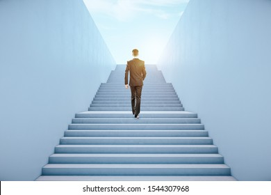 Back view of young businessman climbing abstract bright concrete sky stairs. Career development and growth concept