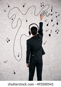 Back view of young businessman with creative sketchings of headphones, player and musical notes. Music concept
