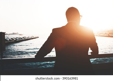 Back view of a young businessman is enjoying view and rest after meeting during his business trip. Silhouette of a male lawyer is resting after work day, while is standing outdoors against sunset