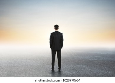 Back view of young businessman looking into the distance on abstract background. Research concept