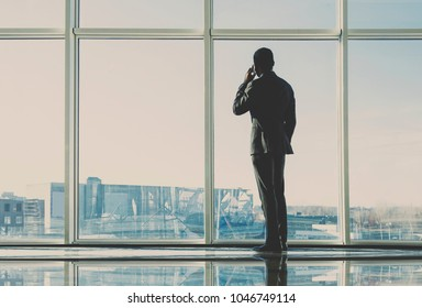 Back view of young businessman is looking out of a panoramic window and talking by phone.