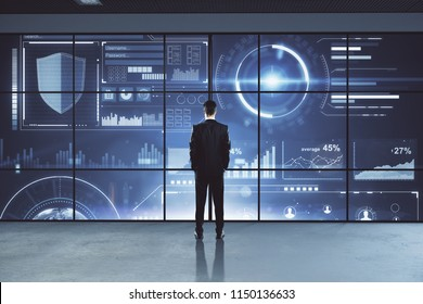 Back view of young businessman looking out of window with digital business hologram view. Future and finance concept.