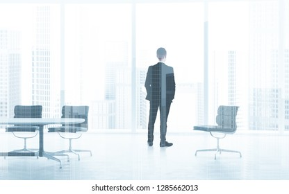 Back view of young businessman looking out the window