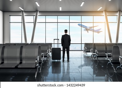 Back view of young businessman looking out of window in modern airport lounge interior with daylight, suitcase and airplane. Travel and vacation concept.