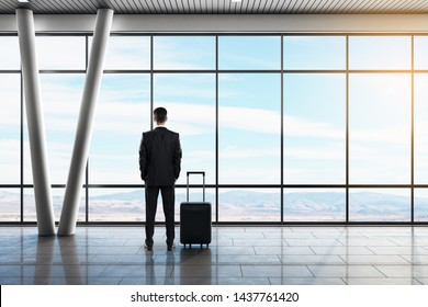 Back view of young businessman looking out of window in contemporary airport lounge interior with daylight, suitcase and airplane. Travel and vacation concept.