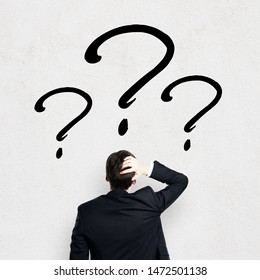 Back view of young businessman looking at black question marks on white wall background. Confusion and faq concept