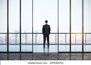 Back view of young businessman looking out of window in clean empty office interior with panoramic city view and daylight. Research concept.