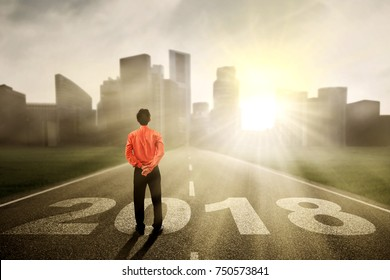 Back view of young businessman looking at sunlight while standing above numbers 2018 on the paths
