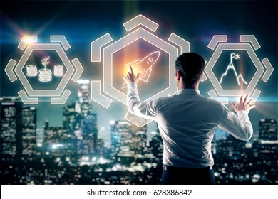 Back view of young businessman managing abstract digital buttons on night city background. Leadership concept