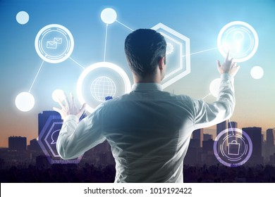 Back view of young businessman on rooftop with business chart hologram. Futuristic innovation and management concept. Double exposure