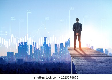 Back view of young businessman on rooftop with business chart hologram. Futuristic innovation and forex concept. Double exposure