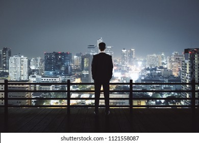 Back view of young businessman on rooftop looking at illuminated night city. Research and success concept